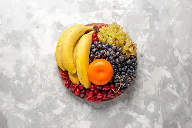 Vista superior composição de frutas bananas frescas dogwoods e uvas na superfície branca frutas baga frescor vitamina Foto gratuita