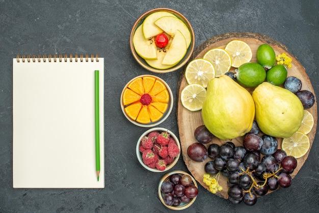 Vista superior composição de frutas diferentes frescas e maduras no fundo cinza escuro frutas maduras planta saudável cor suave