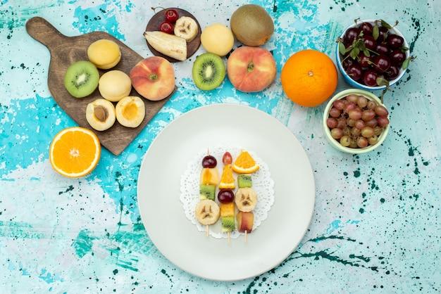 Vista superior composição de frutas fatiadas e inteiras no fundo azul biscoito exótico de frutas