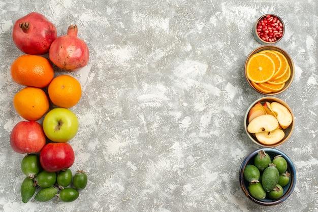 Vista superior composição de frutas feijoa tangerinas e maçãs em uma superfície branca vitamina de frutas maduras maduras