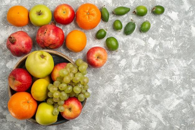 Vista superior composição de frutas feijoa tangerinas e maçãs no fundo branco frutas maduras vitamina suave fresca