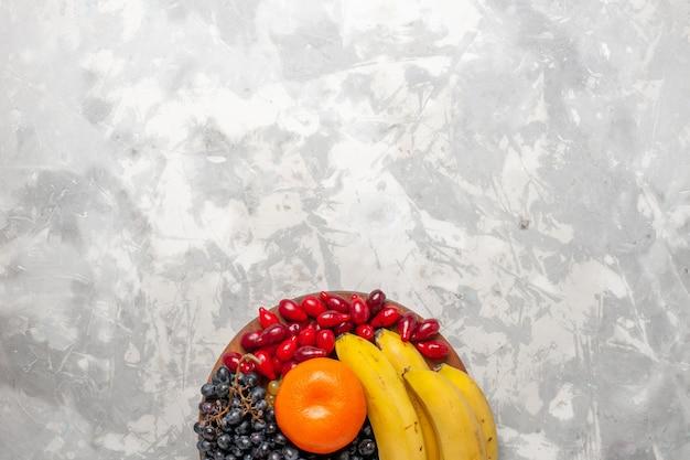 Vista superior composição de frutas frescas bananas dogwoods e uvas na mesa branca vitamina de frescor de frutas baga