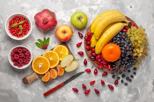 Vista superior composição de frutas frescas bananas dogwoods e uvas na superfície branca clara fruta baga frescura vitamina