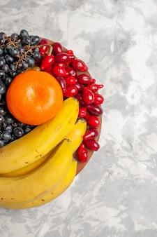 Vista superior composição de frutas frescas bananas dogwoods e uvas na superfície branca vitamina de frescor de frutas baga