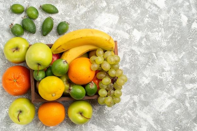 Vista superior composição de frutas frescas bananas uvas e feijoa na mesa branca frutas suaves vitaminas saudáveis frescas