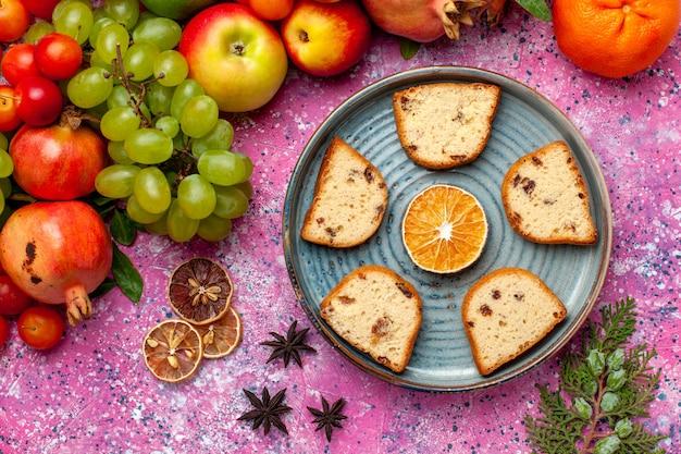 Vista superior composição de frutas frescas frutas coloridas com bolos fatiados mesa rosa