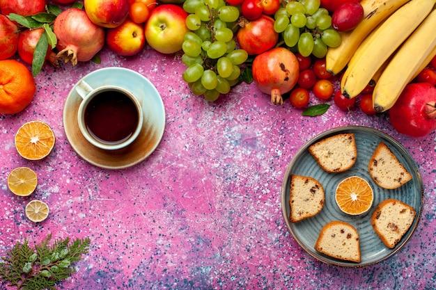 Vista superior composição de frutas frescas frutas coloridas com deliciosos bolos fatiados na mesa rosa