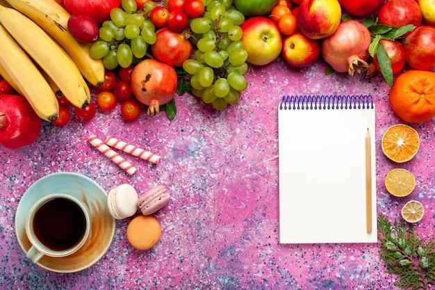 Vista superior composição de frutas frescas frutas coloridas com xícara de chá e macarons na superfície rosa claro