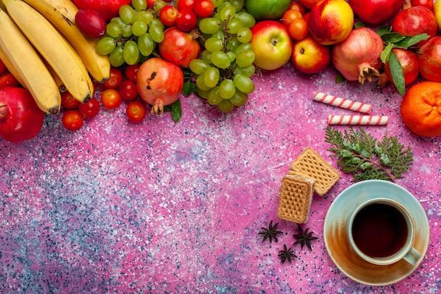 Vista superior composição de frutas frescas frutas coloridas com xícara de chá e waffles na superfície rosa claro