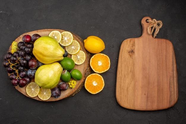 Vista superior composição de frutas frescas frutas maduras e suaves em frutas superficiais escuras vitaminas maduras frescas