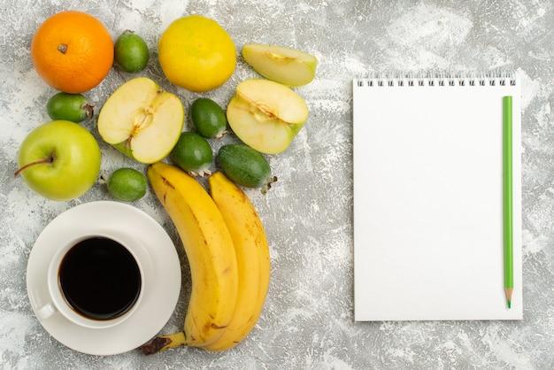 Vista superior composição de frutas frescas maçãs feijoa bananas e outras frutas no fundo branco frutas frescas maduras vitamina de cor