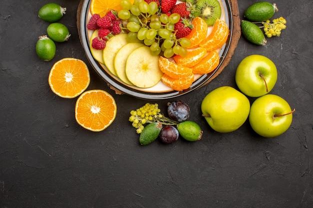 Vista superior composição de frutas frescas maduras fatiadas e frutas maduras na superfície escura frutas maduras vitamina fresca suave