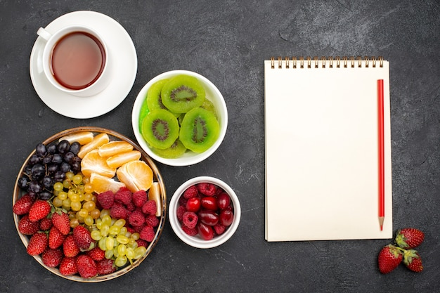 Vista superior composição de frutas morangos uvas framboesas e tangerinas com uma xícara de chá na mesa cinza-escuro