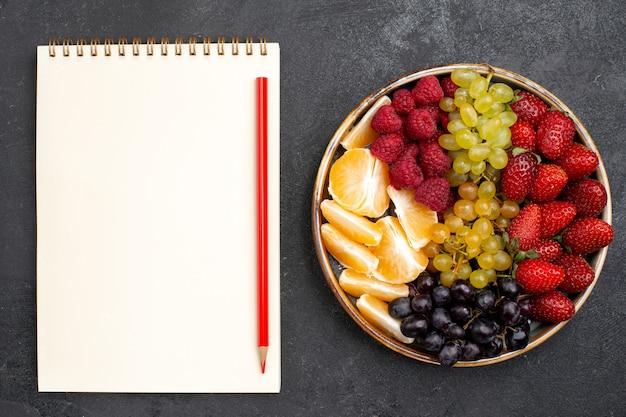 Vista superior composição de frutas morangos uvas framboesas e tangerinas dentro da bandeja no espaço escuro