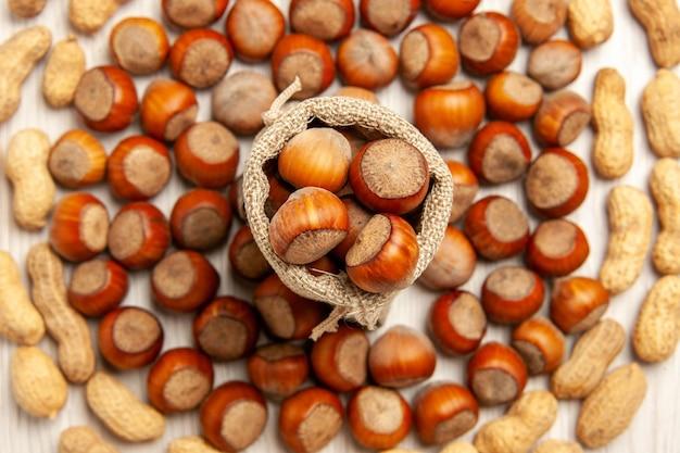 Vista superior composição de nozes avelãs frescas e amendoim na mesa branca, porca lanche amendoim noz