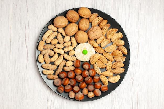 Vista superior composição de nozes nozes frescas, amendoins e avelãs dentro da placa na mesa branca, porca, lanche, planta, árvore, muitos, shell