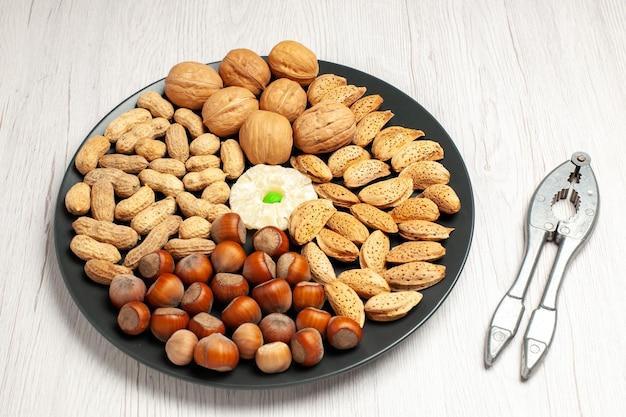 Vista superior composição de nozes nozes frescas, amendoins e avelãs dentro do prato na mesa branca, árvore de nozes, planta de lanche muitas conchas