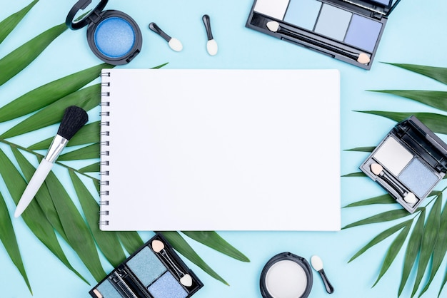 Vista superior composição de produtos de beleza diferentes com o bloco de notas vazio