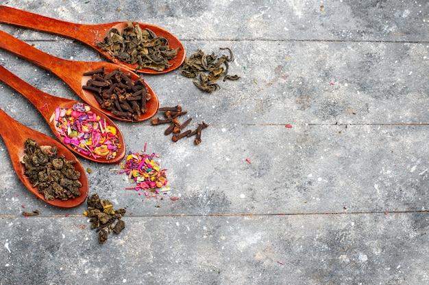 Vista superior composição de temperos de cores diferentes dentro de colheres na mesa rústica cinza cor de planta seca de chá