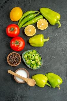 Vista superior composição de vegetais tomate pimentão e limão em fundo escuro