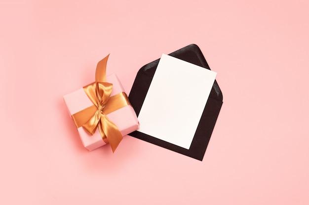 Vista superior composição festiva com belo presente embrulhado em papel de férias, fita de ouro e envelope preto com modelo de papel-de-rosa