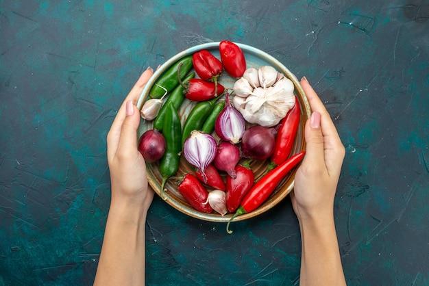 Vista superior composição vegetal cebolas alhos pimentas tocadas por uma fêmea na mesa escura salada de vegetais cor de refeição