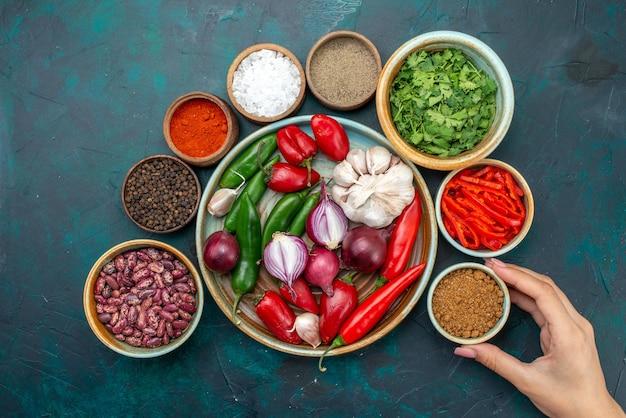 Vista superior composição vegetal cebolas alhos verdes e pimentas na mesa escura, foto colorida de salada de comida de vegetais