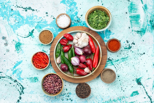 Vista superior composição vegetal pimentas cebolas alhos e verduras na mesa azul claro comida refeição ingrediente salada