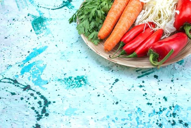 Vista superior composição vegetal repolho cenouras verdes e pimentão vermelho picante na mesa azul brilhante comida vegetal cor saudável