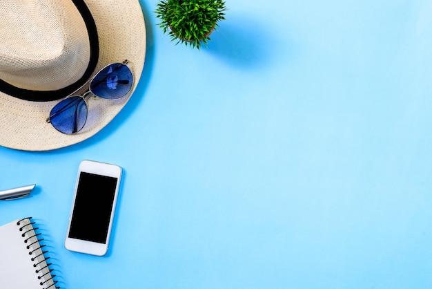 Vista superior, conceito de planejamento de viagens de verão com chapéu branco, óculos azuis, telefone e notebook