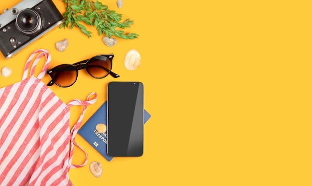 Vista superior conceito de viagens com filmes de câmera retro, passaporte, telefone e parte superior listrada das mulheres, óculos de sol, conchas sobre fundo amarelo, com espaço de cópia, fundamentos turísticos. conceito de férias de verão