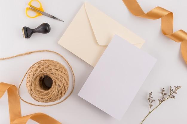 Vista superior, configuração lisa, cartão do convite do casamento, envelopes, papéis de cartões no fundo branco.