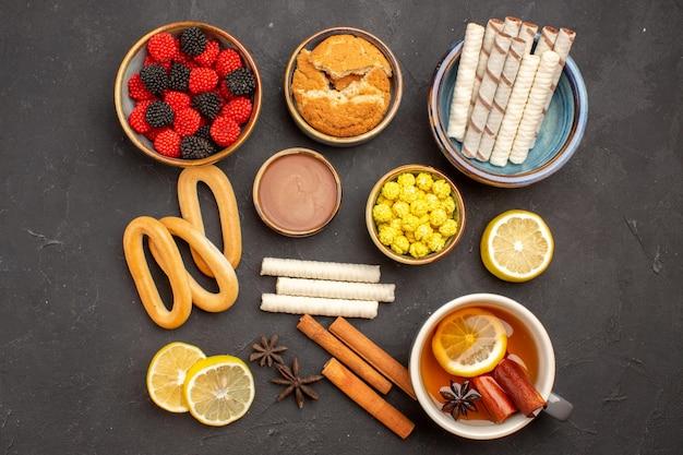 Vista superior confiture de doces com uma xícara de chá e biscoitos na superfície escura.