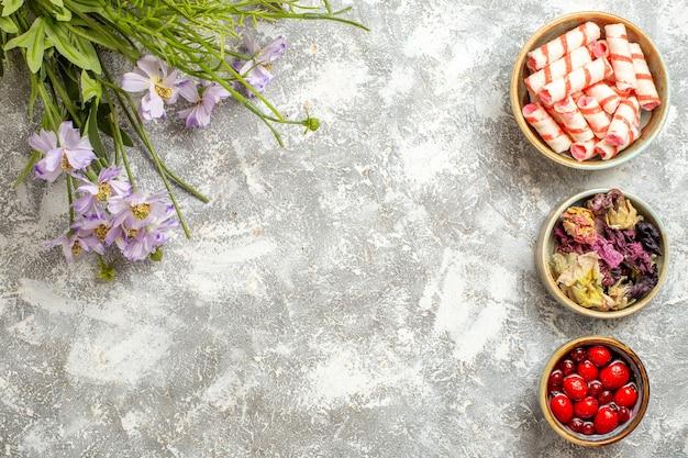 Vista superior confitures com geleia e flores na superfície branca.
