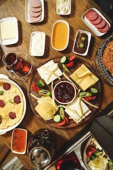Vista superior conjunto café da manhã queijos geléia de salsicha mel creme de leite legumes com ovos mexidos e chá na mesa