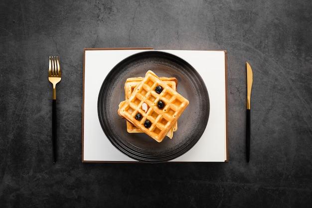 Vista superior conjunto de dois waffles com talheres de ouro