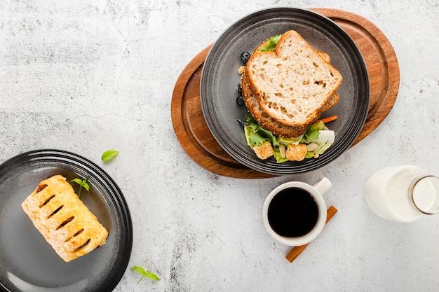 Vista superior conjunto de sanduíche ao lado de caneca de café