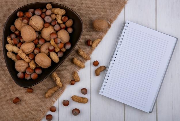 Vista superior cópia espaço amendoins com avelãs e nozes em uma tigela com um notebook em um fundo cinza