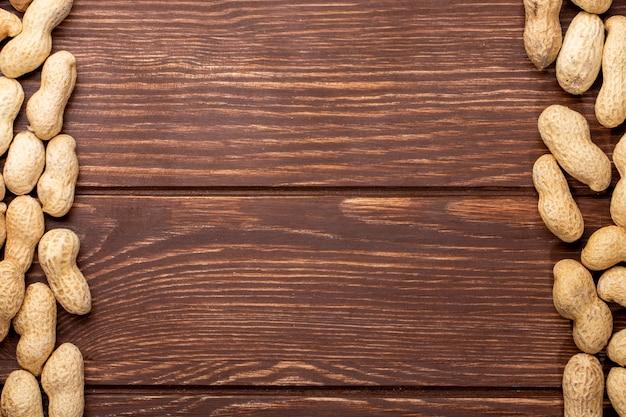 Vista superior cópia espaço amendoins com casca em uma mesa de madeira