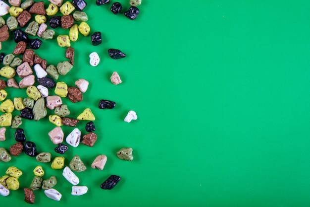 Vista superior cópia espaço bombons de chocolate em forma de uma pedra sobre um fundo verde