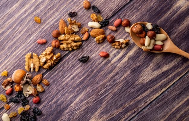 Vista superior cópia espaço colher de madeira com nozes e passas de amendoins e amêndoas em uma mesa de madeira