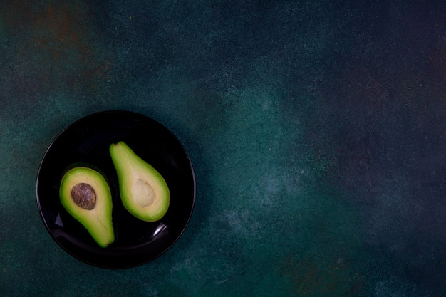 Vista superior cópia espaço cortado ao meio abacate em uma placa preta sobre um fundo verde escuro