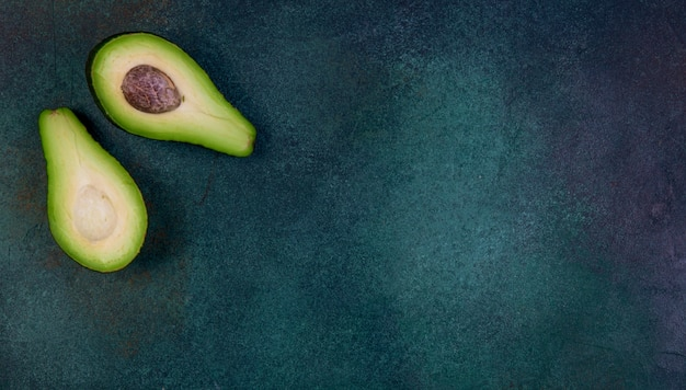 Vista superior cópia espaço cortado ao meio abacate sobre um fundo verde escuro