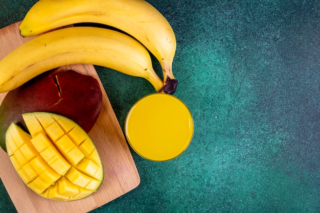 Vista superior cópia espaço fatiado manga com bananas a bordo com suco de laranja em verde