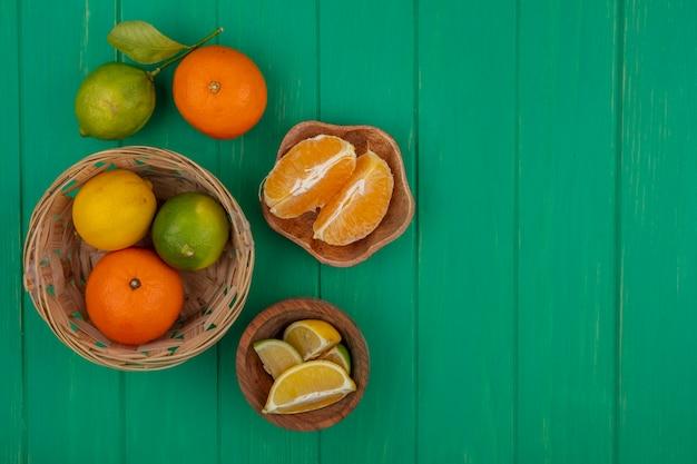 Vista superior cópia espaço fatias de laranja descascadas em uma tigela com laranja limão e limão em uma cesta sobre um fundo verde