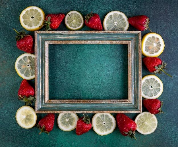 Vista superior cópia espaço fatias de limão e limão com morangos ao redor do quadro, sobre um fundo verde