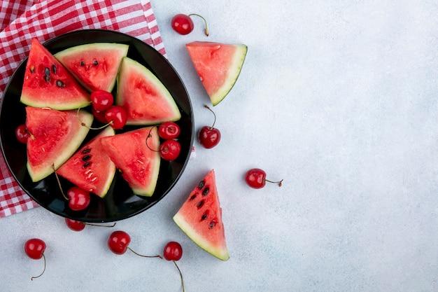 Vista superior cópia espaço fatias de melancia com cerejas em um prato preto