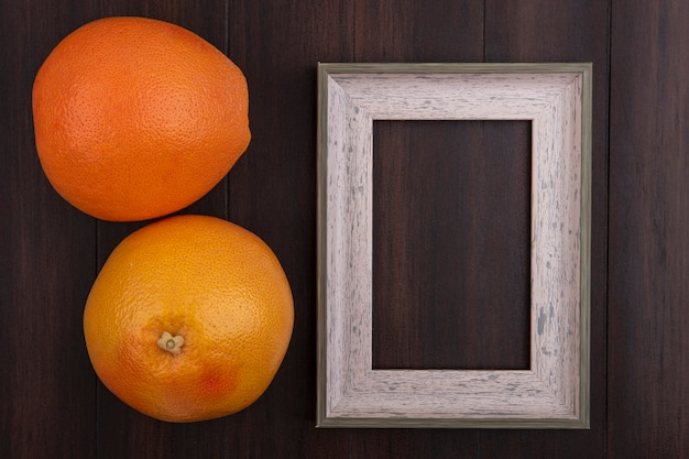 Vista superior cópia espaço laranjas com moldura cinza em fundo de madeira