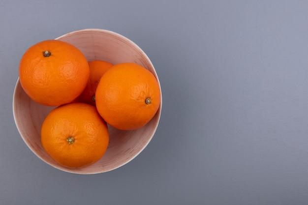 Vista superior cópia espaço laranjas em uma tigela em fundo cinza