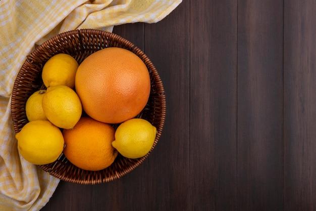 Vista superior cópia espaço limões com laranja e toranja em uma cesta com toalha amarela quadriculada em fundo de madeira